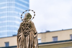 Immaculate conception statue of Virgin Mary with nimbus halo with modern skyscraper building in blurry blurred bokeh background at Church of St. Anthony of Padua, Warsaw Poland