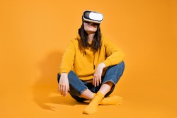 Immersion in cyberspace, virtual reality and the user. A gamer in a yellow hoodie and with a VR helmet on a head sits on a yellow background.