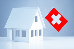 Immigration abroad. Miniature house with the flag of Switzerland. To leave for permanent residence to Switzerland. Resettlement to Switzerland. Accommodation in Europe. Emigration.
