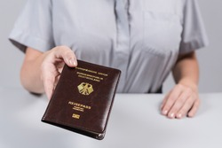 Immigration and passport control at the airport. woman border control officer with Deutsch passport of German citizen. Concept