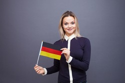 Immigration and the study of foreign languages, concept. A young smiling woman with a Germany flag in her hand. Girl waving a German flag on a gray background