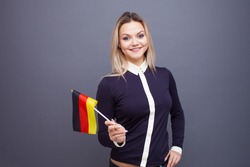 Immigration and the study of foreign languages, concept. A young smiling woman with a Germany flag in her hand. woman waving a German flag on a gray background