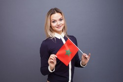 Immigration and the study of foreign languages, concept. A young smiling woman with a Morocco flag in her hand. woman waving a Moroccan flag on a gray background