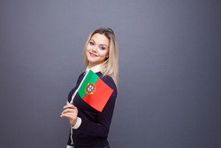 Immigration and the study of foreign languages, concept. A young smiling woman with a Portugal flag in her hand. woman waving a Portuguese flag on a gray background