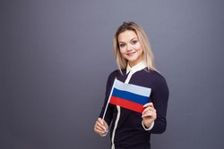 Immigration and the study of foreign languages, concept. A young smiling woman with a Russia flag in her hand. woman waving a Russia flag on a gray background