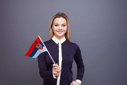 Immigration and the study of foreign languages, concept. A young smiling woman with a Serbia flag in her hand. woman waving a Serbian flag on a gray background