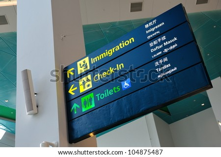 Immigration, check-in and toilet signs in Marina Bay Cruise Center Singapore in 4 languages