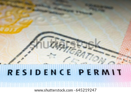 Immigration concept image. Residence permit card over immigration stamp on UK student visa in passport. Selective focus