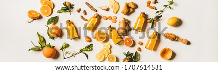 Immune boosting natural vitamin health defending drink. Flat-lay of fresh turmeric, ginger and citrus juice shots over white background, top view, wide composition. Vegan Immunity system booster