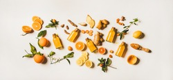 Immune boosting natural vitamin health defending drink to resist virus. Flat-lay of fresh turmeric, ginger and citrus juice shots over white background, top view. Vegan Immunity system booster