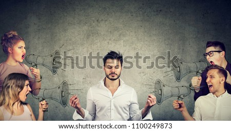 Impassive meditating young businessman paying no attention to crowd of screaming in megaphone angry people