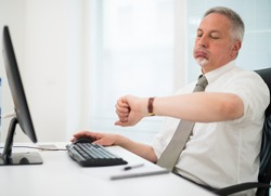 Impatient businessman watching his wrist watch in the office