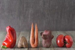 Imperfect red pepper, carrot,  sweet potato, red tomato arranged in a row on a wooden background. Food concept, imperfect produce concept.Image with copy space.