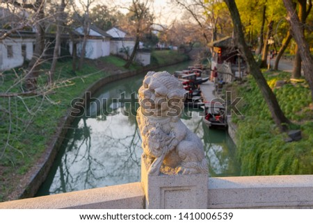 Imperial guardian Lion sculpture with boats moored to the pier i #1410006539