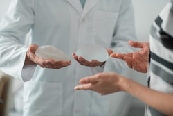 Implants for breast. Plastic surgeon wearing white lab coat holding implants for breast showing them to client