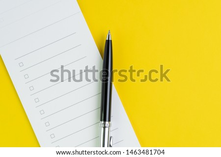 Important business checklist, planning for shopping reminder or project priority task list, black pen on small notepad with checkbox on solid yellow background with copy space.