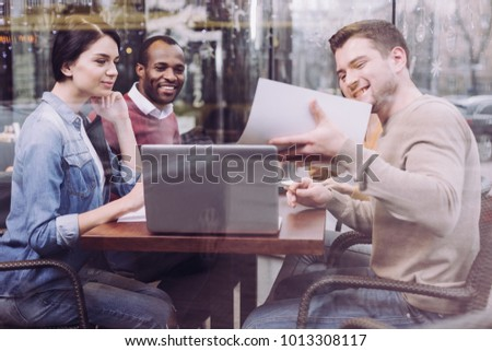 Important data. Nice pretty three colleagues staring at document while sitting at cafe and grinning - Shutterstock ID 1013308117