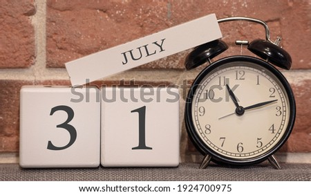 Important date, July 31, summer season. Calendar made of wood on a background of a brick wall. Retro alarm clock as a time management concept. Zdjęcia stock ©