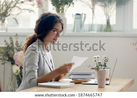 Important message. Focused attentive young woman florist designer sitting at work desk in office studio. Small business owner involved in reading paper letter from bank of credit loan terms conditions Foto stock ©