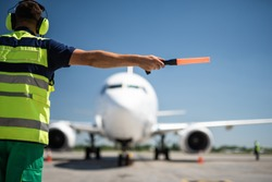 Important signal. Back view of airport worker meeting aircraft and showing right position for landing