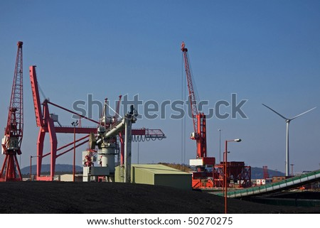 Imported coal alongside a wind turbine at the Port of Bristol Avonmouth docks UK