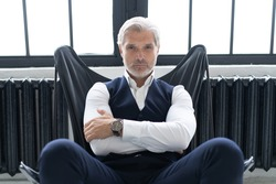 Imposing mature man in elegant suit sitting on a leather chair in a modern luxurious interior. Fashion. Business