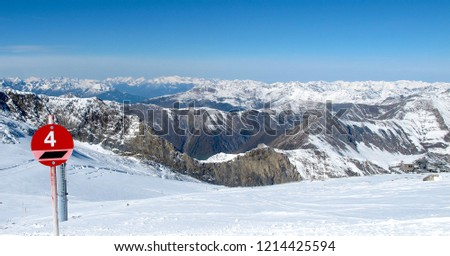 Imposing view of Hintertux Glacier ski slopes with rocky mountains, snow, clouds and a slope marker.   #1214425594