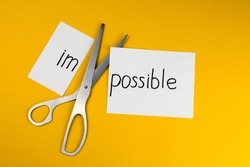 Impossible Is Possible Concept. card with the text impossible, cutting the word im so it written possible.