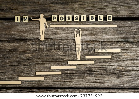 Impossible - Possible creative concept with two paper cutouts of men with one pushing away the letters IM while the second stands on steps supporting the rest of the text on a wooden background. #737731993