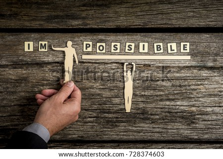 Impossible - Possible teamwork concept with businessman holding paper cut out of men while pushing away the letters IM. #728374603