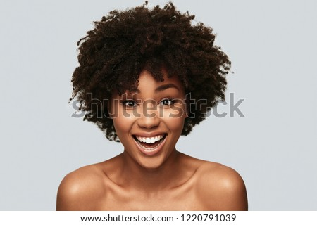 Impossible to resist her. Attractive young African woman looking at camera and smiling while standing against grey background