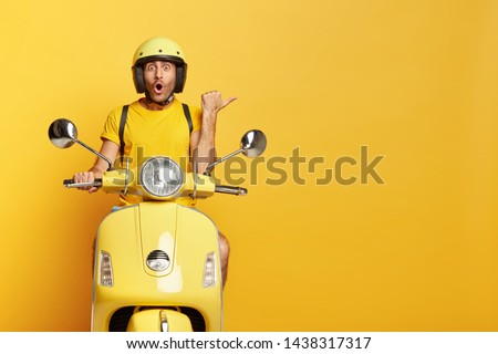 Impressed driver covers distance on yellow motorbike, wears helmet, indicates with great wonder aside, stops on road, demonstrates blank space for your advertising content, tries new vehicle.