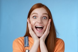 Impressed excited overwhelmed young redhead girlfriend fan screaming thrilled express afection adore awesome music band yelling happily reacting surprised astonished, standing blue background.