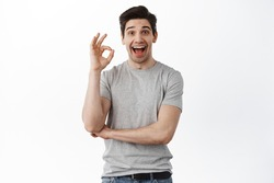 Impressed happy man say yes, show okay sign and nod in approval, satisfied with good result, praise excellent thing, standing against white background