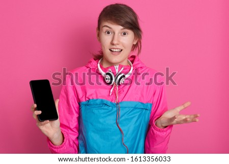 Impressed shocked dark haired hipster girl surprised to listen shocking news, has headphones around neck and smart phone wirh blank screen in hand, isolated over pink studio wall. Copy space.