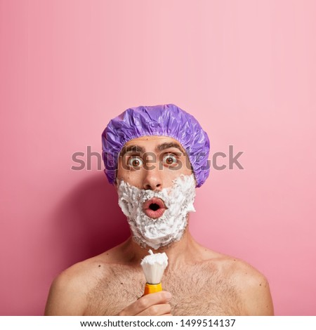 Impressed shocked young male model applies shaving gel on face, holds brush, stares with bugged eyes, wears protective headgear has bare shoulders stares surprisingly at camera copy space on pink wall