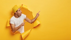 Impressed young man points away, shows direction somewhere, gasps from wonderment, has anxious worried facial expression, dressed in white t shirt and headgear, poses in torn hole of paper wall