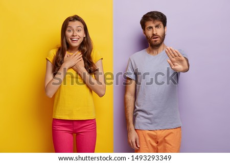 Impressed young woman feels excited and happy, keeps hands on chest, serious unshaven man makes stop gesture, stand closely to each other against colorful studio wall. Emotions, reaction concept