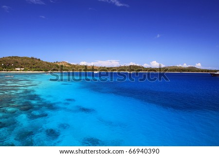 impressing blue water of the sea with a reef and a wonderful sandy beach in the background