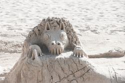 impressing sculpture of a cute dragon made of sand on the beach