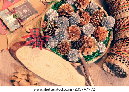 Impression arrangement with natural material, Christmas pine cone in art basket, wooden pen to send message onto oval board,  Xmas card make vintage style for decoration