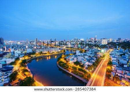 Impression, colorful, vibrant scene of Asia traffic, dynamic, crowded city with trail on street, Nhieu Loc channel, Ho Chi Minh city (aka Saigon) at blue hour, Vietnam