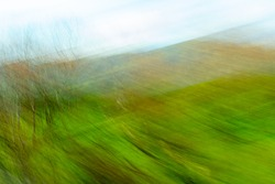 Impressionist landscape photography using intentional camera movement creating texture and effect for abstract, background or artistic use taken from moving train between Wellington and Auckland.