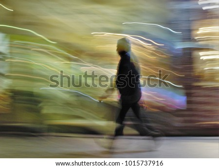 Impressionist night photography of people taken at low speed, in a commercial street, with lights, ghostly shadows, panoramic, blurred background, motion sensation, semi-brutish person,in Toledo,Spain