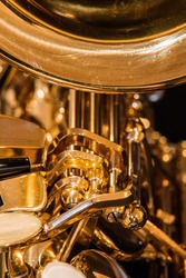 Impressionistic composition of the mechanical workings of a shiny brass saxophone
