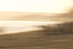 impressionistic deliberate blur of sandy beach and sea at sunset