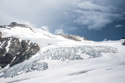 Impressive and strong glacier in Siwss Alps in a summer day with still lots of cold and ice high up