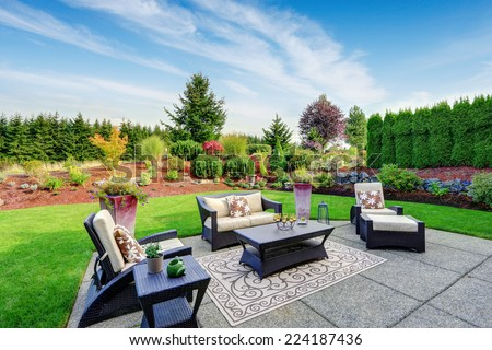 Impressive backyard landscape design. Cozy patio area with settees and table