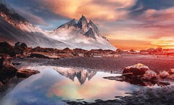 Impressive colorful sunset of Iceland. Dramatic view on magic rocky mount and perfect reflection. with clouds during sunrise. Amazing nature landscape near Stokksnes cape and Vestrahorn Mountain.