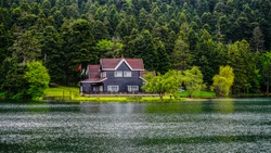 Impressive lake house. House on the shore of Cennet Gol (Paradise Lake), Bolu. Reflected on water. Country side, forest and farm field, lake with house. Traditional government building on lake coast.